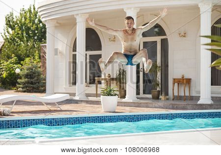 Happy young man jumping into the swimming pool.