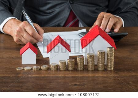 Businessman Calculating Tax By House Models And Coins