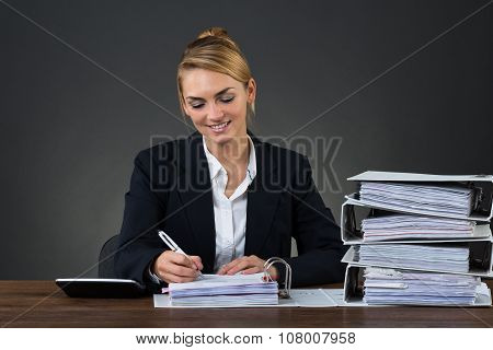Businesswoman Writing On Document At Desk
