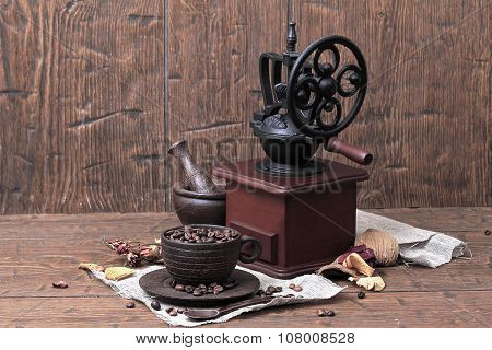 Vintage Coffee Grinder, Cup, Saucer, Mortar, Pestle, Spoon And Coffee Is Lying Beans On Homespun Can