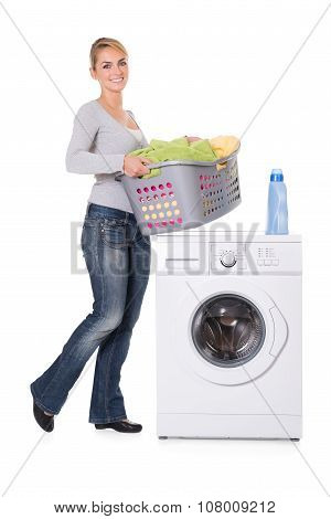 Woman With Detergent And Laundry Standing By Washing Machine