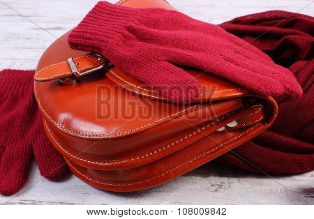 Woolen Gloves And Shawl With Leather Handbag For Woman On Old Wooden Background