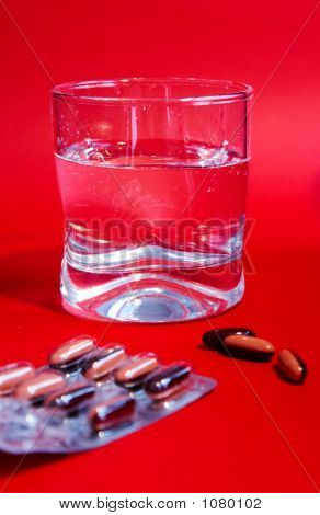 A Glass Of Water And Medicines On Red Background