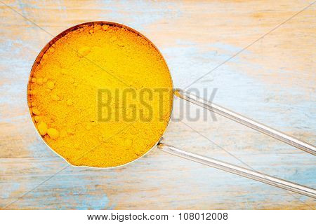 turmeric root powder on a metal measuring scoop over wood background