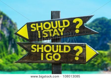 Should I Stay? Should I Go? signpost in a beach background