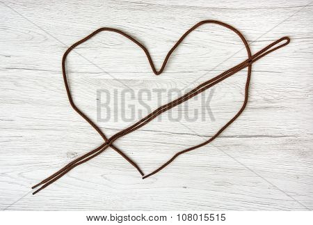 Brown Shoelaces Shaped In The Heart On The Wooden Background, Valentine's Day