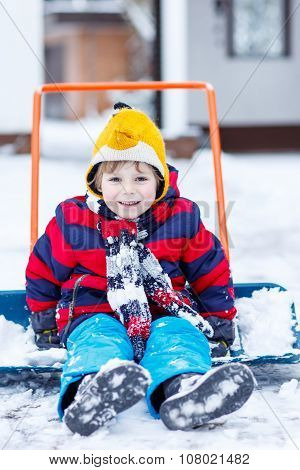 Funny Kid Boy Having Fun With Riding On Snow Shovel, Outdoors