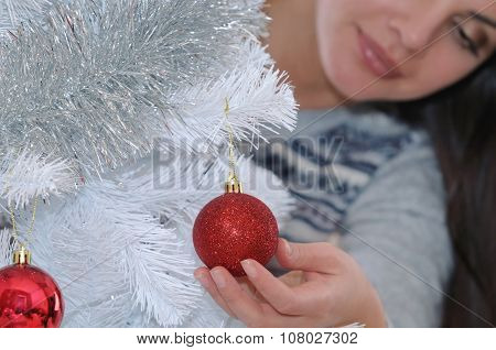 Cropped Shot Of Young Woman Decorating Her Christmas Tree At Home
