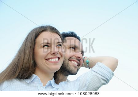 Happy Young Couple Looking In One Direction Outdoors On Blue Sky Background
