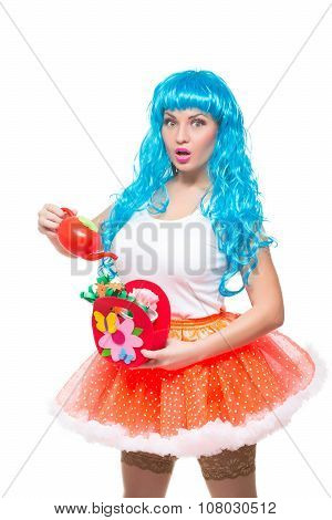 young girl doll with blue hair. watering artificial flowers