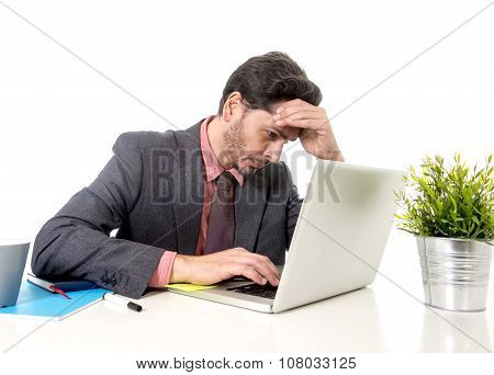 Businessman In Suit And Tie Sitting At Office Desk Working On Computer Laptop Looking Concentrated A