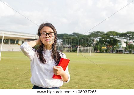 Young and happy female student with book on grass field