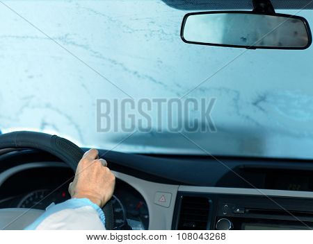 Woman driving with frozen windshield.  Driver insurance concept.