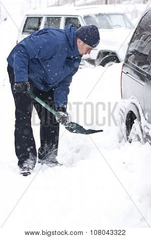 Man with a snow shovel. Car and street under snow.