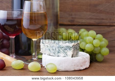 Wine pouring into wine glass. Cheese, grapes in restaurant.