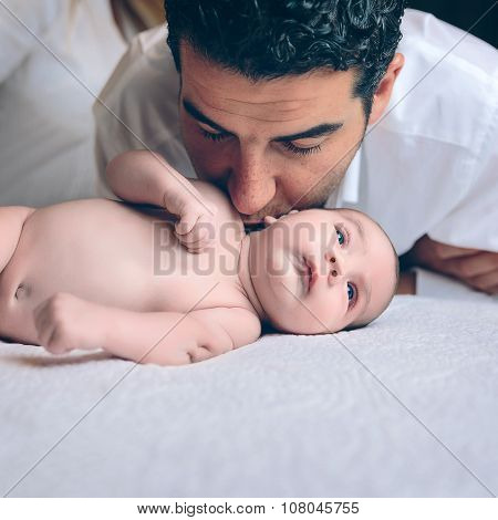 Man kissing to peaceful newborn lying over bed