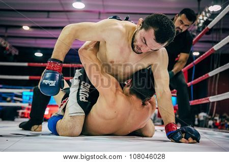 two fighters mixed martial arts fight on floor of  ring