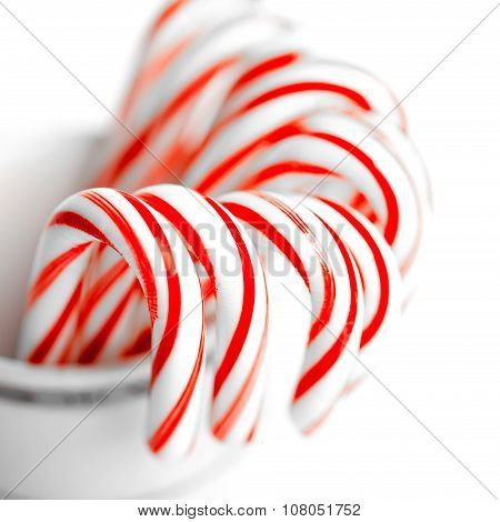 White and red peppermint candy canes in bucket
