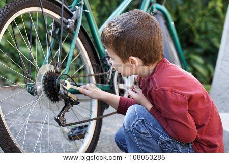 Little Boy Repair Bicycle Outdoor