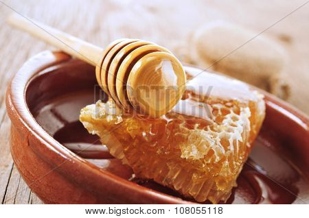 closeup of a honeycomb and a honey dipper with honey in an earthenware plate placed on a rustic wooden surface