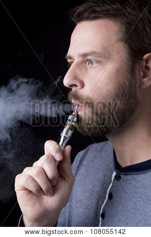 smoking electric cigarettes on the black background