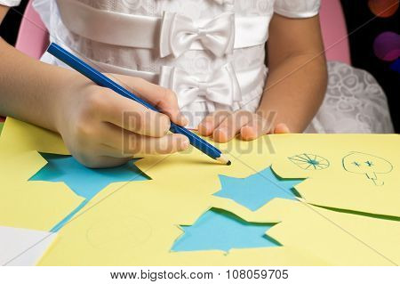 Hands Of Little Girl Drawing And Cutting Christmas Paper Figures
