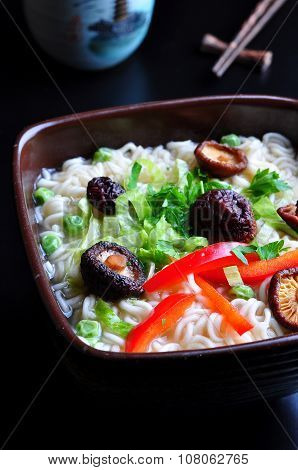 ramen noodles with shiitake mushrooms, green peas, sweet pepper and coriander