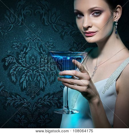 Noble beautiful woman with martini glass on damask wallpaper background