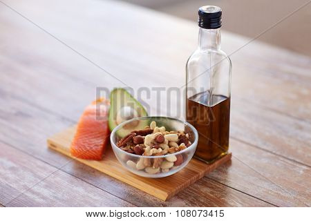 healthy eating, diet and culinary concept - close up of salmon fillets, avocado, olive oil bottle and nuts in glass bowl on table