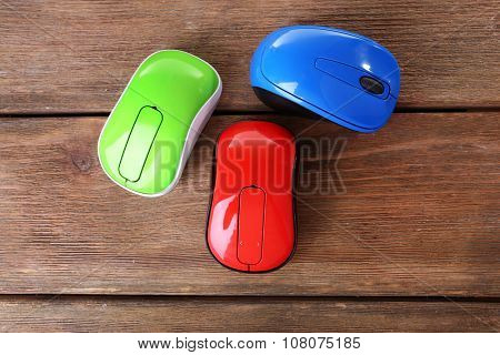 Colourful wireless computer mouses on wooden background
