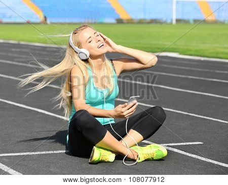 Young woman listening to music on the stadium