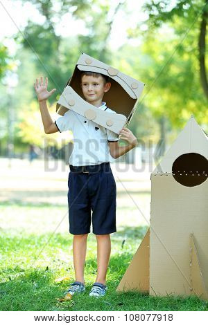 Funny boy in carton helmet standing near carton rocket in  the park
