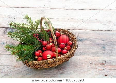 Red Baubles To Decorate The Christmas Tree In A Basket On Rustic Wood