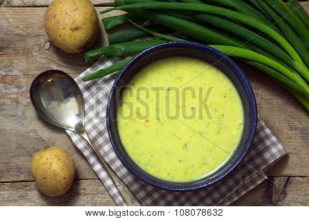 Leek Cream Soup With Spring Onions And Potatoes On Rustic Wood