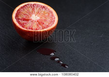 red sicilian orange sliced on slate board with juice drops