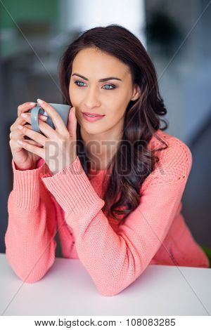 Beautiful woman at home enjoying a cup of coffee