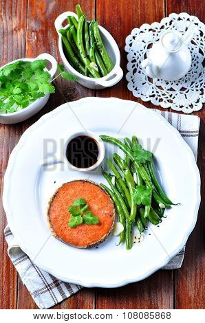 Salmon steak with green beans, garlic, black sesame and soy sauce. Selective focus.