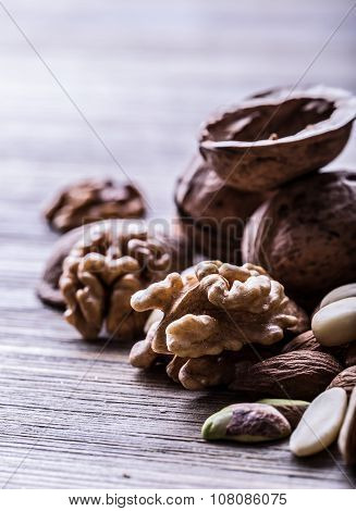 Almonds, walnuts and hazelnuts on a wooden table.