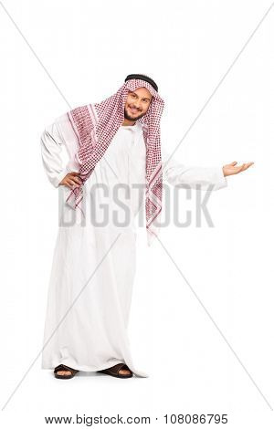 Full length portrait of a young Arab in a white robe and checkered veil gesturing with his hand and looking at the camera isolated on white background