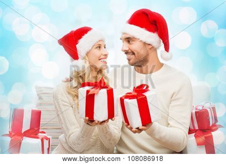 christmas, holidays and people concept - happy couple in santa hats exchanging gifts over blue holidays lights background