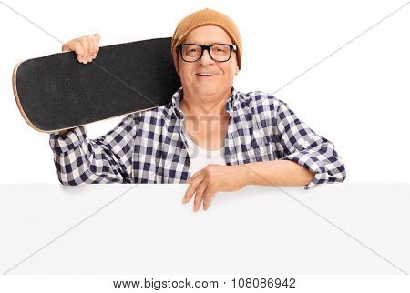 Studio shot of a senior skater holding a skateboard and posing behind a blank panel isolated on white background