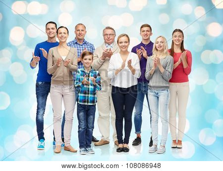 family, gender, generation and people concept - group of smiling men, women and boy applauding over blue holidays lights background