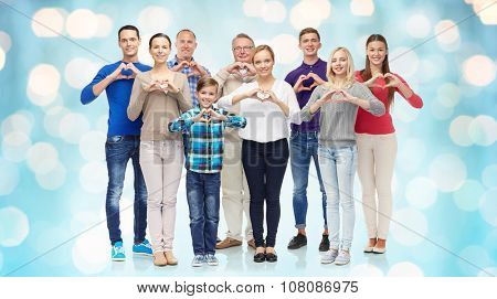 gesture, family, generation and people concept - group of smiling men, women and boy showing heart shape hand sign over blue holidays lights background