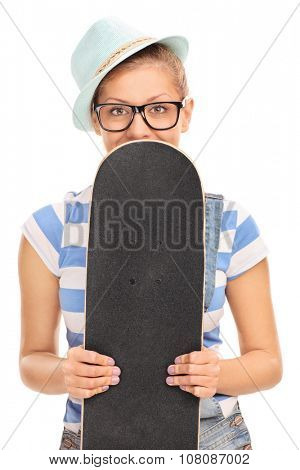 Vertical shot of a blond hipster girl holing a skateboard in front of her face and peeking from behind it isolated on white background