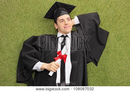 Young college graduate lying on grass with diploma in his hand and daydreaming