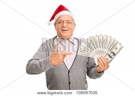 Senior gentleman with Santa hat spreading a stack of money with one hand and pointing towards it with the other isolated on white background