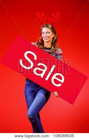 Cheerful pretty young woman wearing Christmas deer horns holding sale board. Beauty, fashion. Shopping.