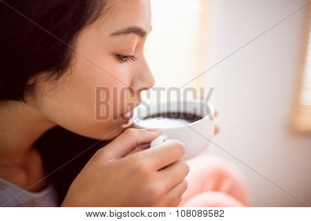 Asian woman relaxing on couch with coffee at home in the living room