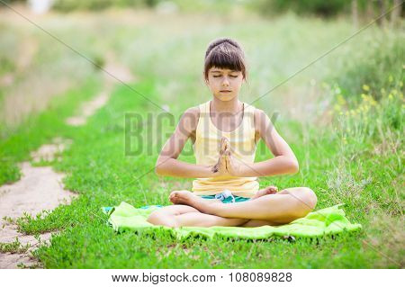 Little girl relaxing while sitting in lotus positionon.