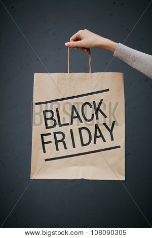 Female hand with paperbag announcing Black Friday